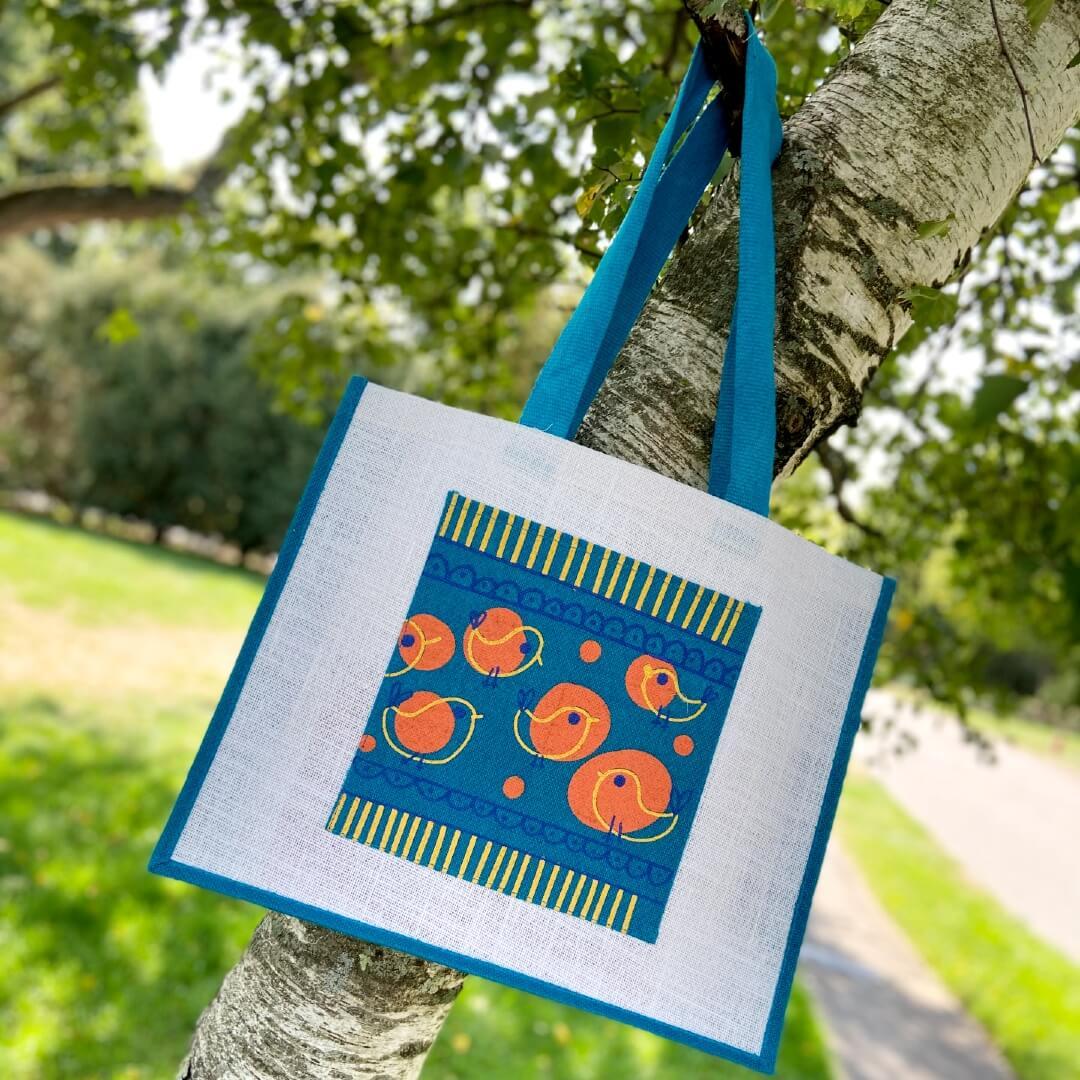 Teal jute tote bag hanging on tree